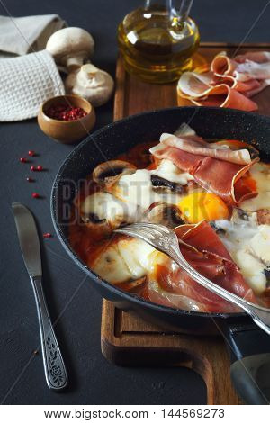 Hearty breakfast: fried eggs with mushrooms and meats
