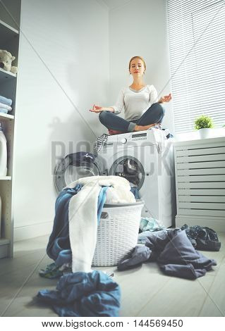 concept. tired housewife meditates in lotus position in laundry room near washing machine and dirty clothes