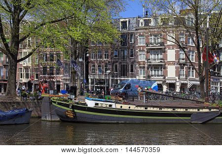 AMSTERDAM, NETHERLANDS - MAY 4, 2016: Houseboat museum and old houses of traditional architecture along canal in Jordan neighborhood, Amsterdam, Netherlands.