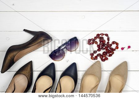 Women accessories and shoes on light background. Top view. Copy space for text.