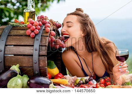 Beautiful woman tasting grapes lying on the grass with lots of tasty italian food and wine in the countryside in Tuscany.