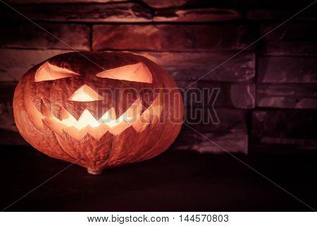 Luminous halloween Jack O' lantern in dark on stone background with copy space