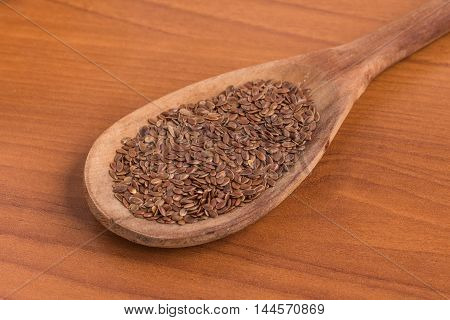 linseed into a spoon over a wooden table