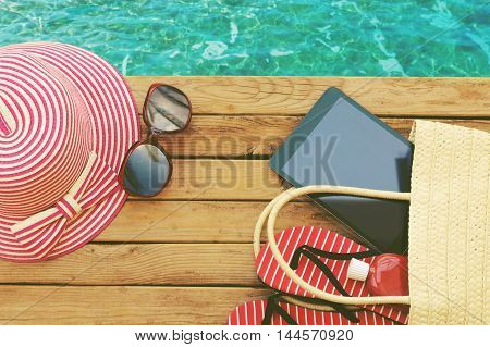 Summer holiday bag with tablet and flip flops on wooden deck. View from above
