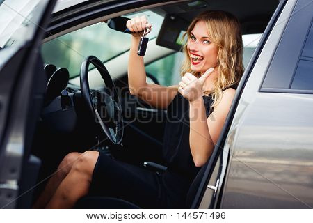 Joyful blond woman sitting behind the wheel, holding car keys and showing thumb up