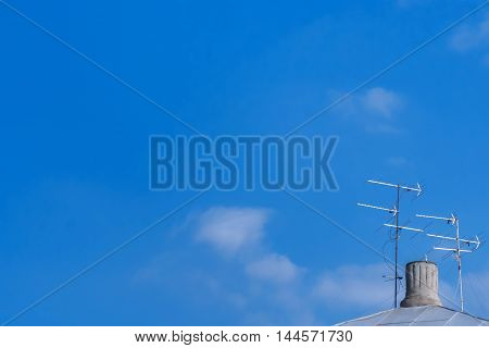 Two TV antennas standing on the roof near the chimney against the blue sky with clouds
