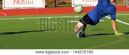 Soccer goalie making a sliding save on a turf field