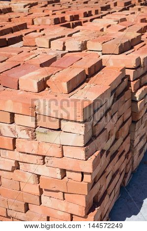 Ceramic red bricks piled in stacks. Material for construction of buildings