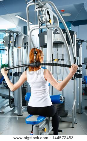 Beautiful girl at the gym exercising on trainers .
