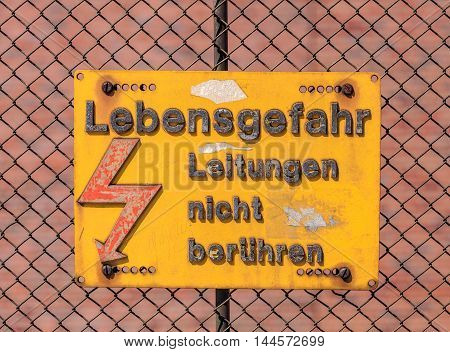 Baselб Switzerland - 27 Augustб 2016: a plate with the high voltage danger warning in German on the fence of a railroad area stating the following