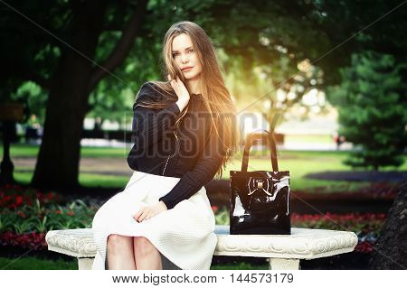 Woman seating on the bench enjoying nature in sunny day outdoors charming young girl relaxing in the summer park female student relaxing at campus flare sun light.