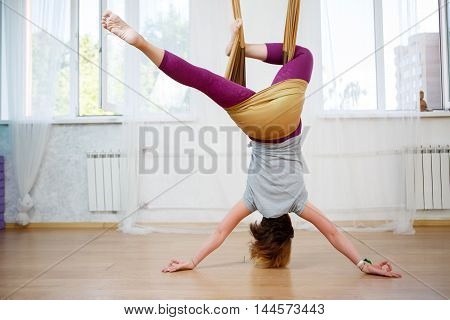 Back view of young caucasian woman posing aerial yoga exercise with hammock in class