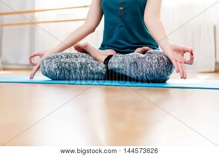 Woman closeup meditating and relaxing in lotus position indoors. Healthy lifestyle concept