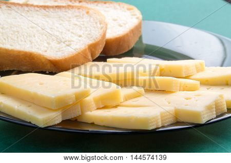 Cut Slices Of Cheese On A Plate Close-up