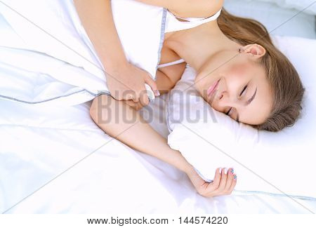 A beautiful young woman lying in bed comfortably and blissfully.