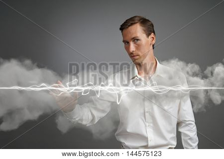 Man in white shirt making magic effect - flash lightning. The concept of electricity, high energy.