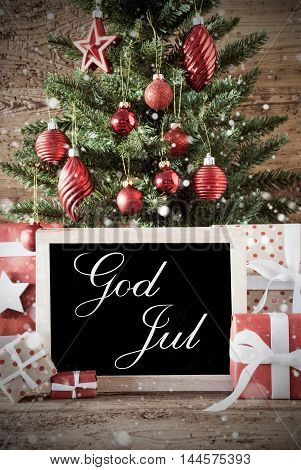 Nostalgic Christmas Card For Seasons Greetings. Christmas Tree With Balls. Gifts Or Presents In The Front Of Wooden Background. Chalkboard With Swedish Text God Jul Means Merry Christmas