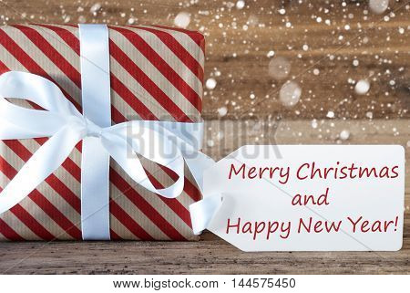 Christmas Gift Or Present On Wooden Background With Snowflakes. Card For Seasons Greetings. White Ribbon With Bow. English Text Merry Christmas And Happy New Year