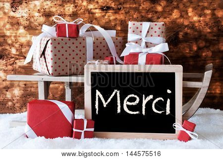 Chalkboard With FrenchText Merci Means Thank You. Sled With Christmas And Winter Decoration. Gifts And Presents On Snow With Wooden Background And Bokeh Effect.