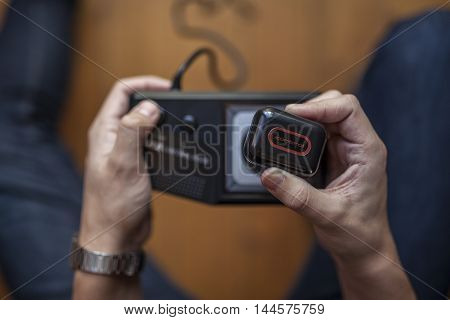 Gothenburg, Sweden - January 7, 2015: A shot from above of an old game pad for the Sega Master System on a wooden floor. The Sega Master System video game console is also visible in the corner.