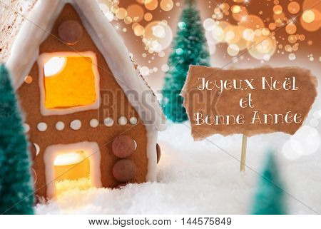 Gingerbread House In Snow As Christmas Decoration. Trees And Candlelight. Bronze And Orange Background With Bokeh Effect. French Text Joyeux Noel Et Bonne Annee Mean Merry Christmas And Happy New Year