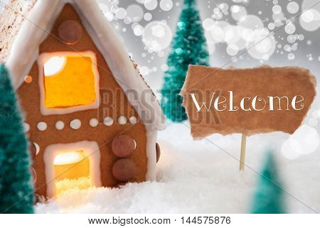 Gingerbread House In Snowy Scenery As Christmas Decoration. Christmas Trees And Candlelight For Romantic Atmosphere. Silver Background With Bokeh Effect. English Text Welcome