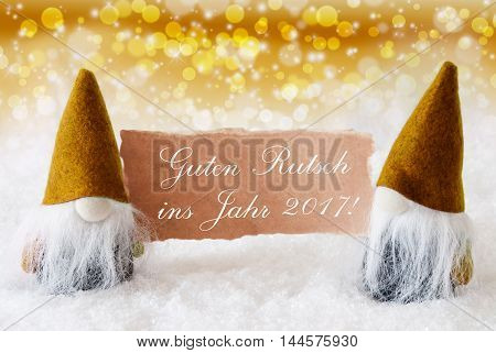 Christmas Greeting Card With Two Golden Gnomes. Sparkling Bokeh And Noble Background With Snow. German Text Guter Rutsch Ins Jahr 2017 Means Happy New Year 2017