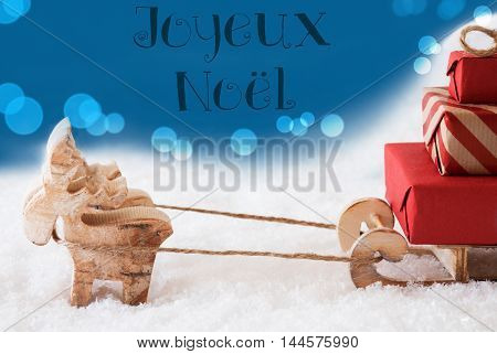 Moose Is Drawing A Sled With Red Gifts Or Presents In Snow. Christmas Card For Seasons Greetings. Blue Background With Bokeh Effect. French Text Joyeux Noel Means Merry Christmas