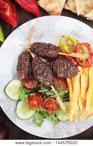 Kofta kebab, turkish minced meat skewer with french fries and vegetable salad
