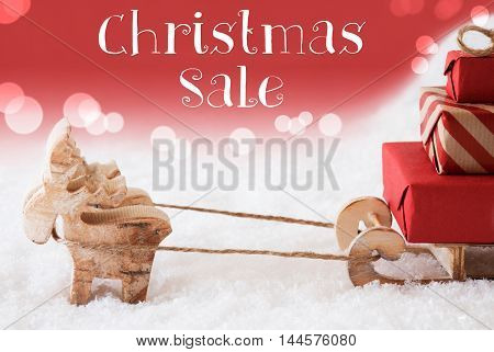 Moose Is Drawing A Sled With Red Gifts Or Presents In Snow. Christmas Card For Seasons Greetings. Red Christmassy Background With Bokeh Effect. English Text Christmas Sale