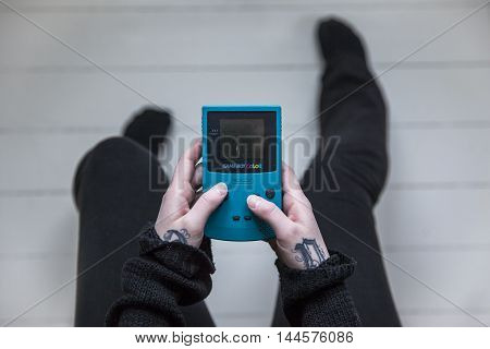 Gothenburg, Sweden - February 20, 2016: A shot from above of a young woman's hands holding a Game Boy Color, a handheld video game console developed by Nintendo in 1998.
