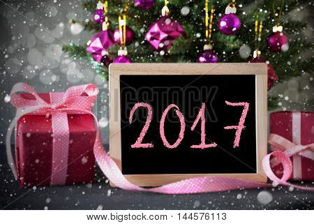 Christmas Tree With Rose Quartz Balls, Snowflakes And Bokeh Effect. Gifts Or Presents In The Front Of Cement Background. Chalkboard With English Text 2017 For Happy New Year
