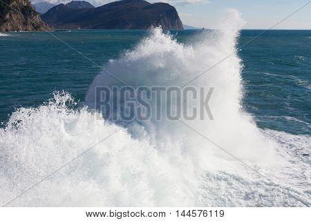 Stone breakwater with breaking waves. Adriatic Sea, Montenegro