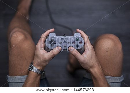 Gothenburg, Sweden - January 31, 2015: A shot from above of a young man's hands as he is using a controller for the Playstation, a video game console developed by Sony Computer Entertainment in 1994.