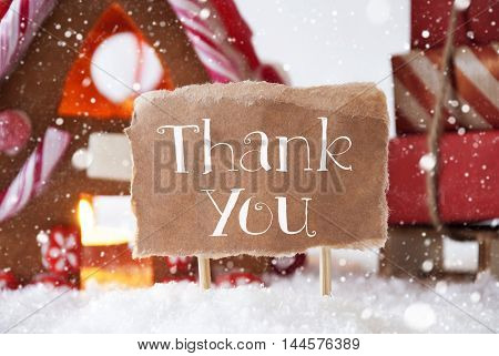 Gingerbread House In Snowy Scenery As Christmas Decoration. Sleigh With Christmas Gifts Or Presents And Snowflakes. Label With English Text Thank You