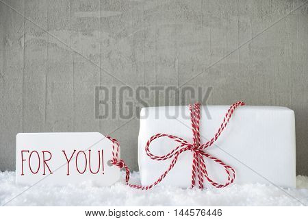 One Christmas Gift Or Present On Snow With Red Ribbon. Cement Or Concrete Wall As Background. Modern And Urban Style. Card For Birthday Or Seasons Greetings. Label With English Text For You