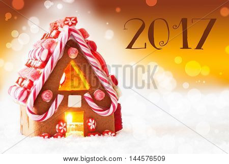 Gingerbread House In Snowy Scenery As Christmas Decoration. Candlelight For Romantic Atmosphere. Golden Background With Bokeh Effect. Text 2017 For Happy New Year