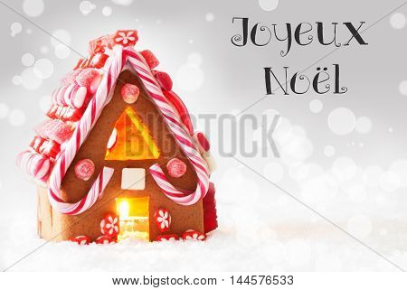 Gingerbread House In Snowy Scenery As Christmas Decoration. Candlelight For Romantic Atmosphere. Silver Background With Bokeh Effect. French Text Joyeux Noel Means Merry Christmas