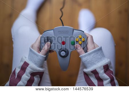 Gothenburg, Sweden - January 11, 2015: A shot from above of a young woman's hands holding a game pad controller for the Nintendo 64 video game console developed by Nintendo Co., Ltd.