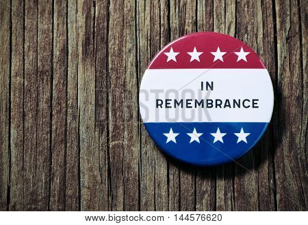 closeup of a pin button with the text in remembrance and the colors and stars of the flag of the United States, on a rustic wooden background