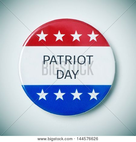 closeup of a pin button with the text patriot day and the colors and stars of the flag of the United States, with a slight vignette added