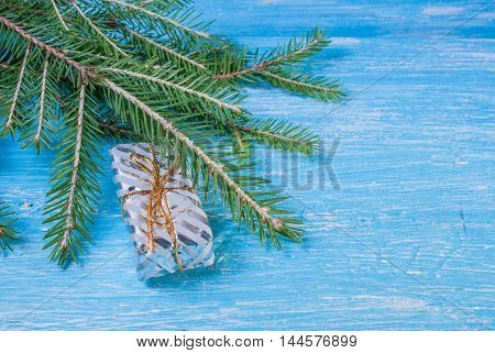 Gift box on a spruce branch. christmas background