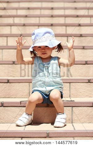 Japanese girl sitting on the stairs (1 year old)