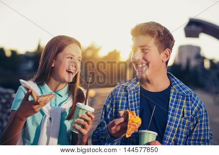 Two cheerful teenagers girl and boy eating pizza outdoor