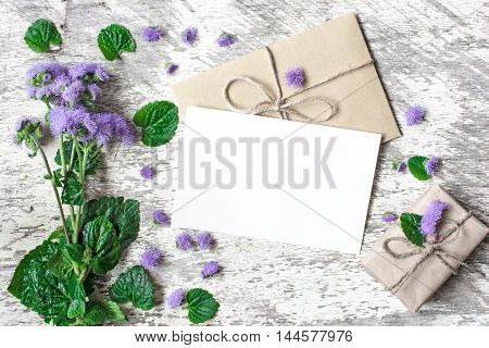 Blank white greeting card and envelope with purple wildflowers and vintage gift box on white rustic wood background with petals around for creative work design