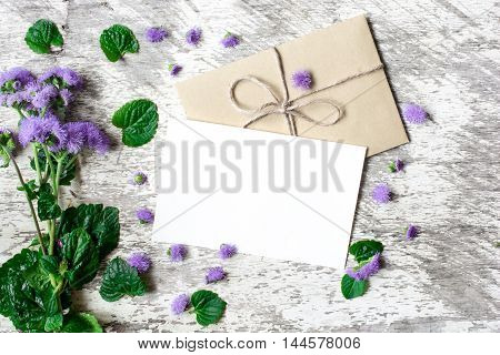 Blank white greeting card and envelope with purple wildflowers on white rustic wood background with petals around for creative work design