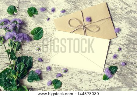 Blank white greeting card and envelope with purple wildflowers on white rustic wood background with petals around. vintage toning