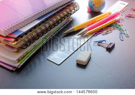 School supplies on blackboard background. Back to school concept with stationery. Notebook stack pens and pencil. Schoolchild and student studies accessories. Back to school concept. Toned image.