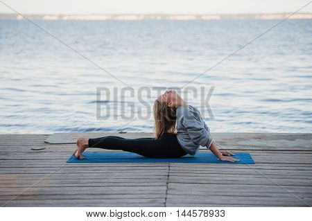 Woman doing stretching yoga exercises in the morning at the sea or lake.