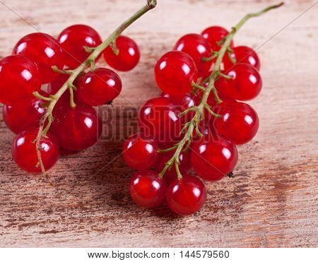 Close-up of red currants on a wooden background.